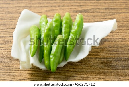 Vegetable, Green Hot Chili or Chilli Cayenne Pepper on Cabbage Leaf. - stock photo