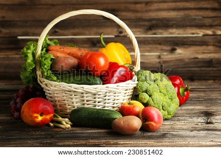 Vegetable in basket on brown wooden background - stock photo