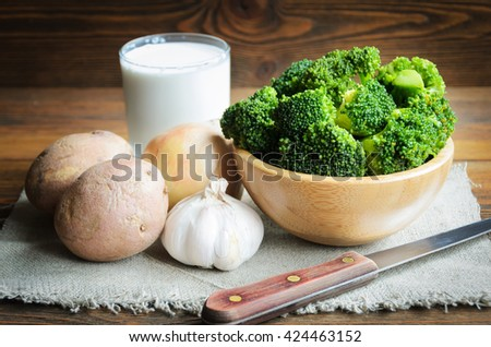 Vegetable ingredients for broccoli cream soup on wooden table - stock photo