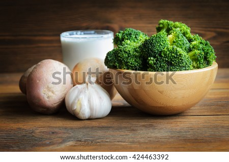 Vegetable ingredients for broccoli soup on wooden background - stock photo