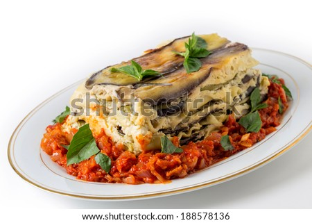 Vegetable lasagne, made with courgettes and eggplants (zucchini and aubergines), pasta sheets and bechamel sauce, served with a tomato and onion sauce and a basil garnish. - stock photo