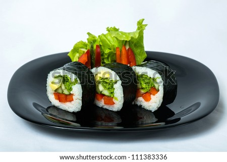 Vegetable maki rolls on a black plate. - stock photo