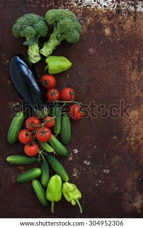 Vegetable mix of garden cherry tomatoes, cucumbers, paprikas, eggplant, broccoli on rusty metal grunge background, top view, copy space - stock photo