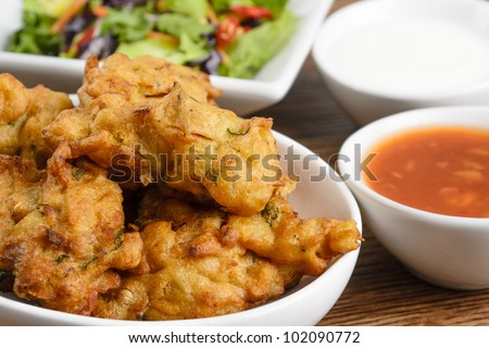 Vegetable Pakora or Onion Bhajis served with salad and chili sauce and yoghurt dip.