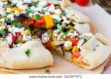 Vegetable pie with eggplant, zucchini, peppers, feta cheese, parsley, Greek dish - stock photo