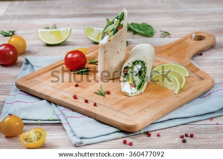 Vegetable rolls of pita. Bread rolls with vegetables inside. The pita bread wrapped cabbage, cucumber, feta cheese. The dish is decorated with lime and tomatoes. - stock photo