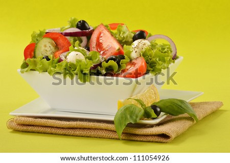 Vegetable salad bowl on green background - stock photo