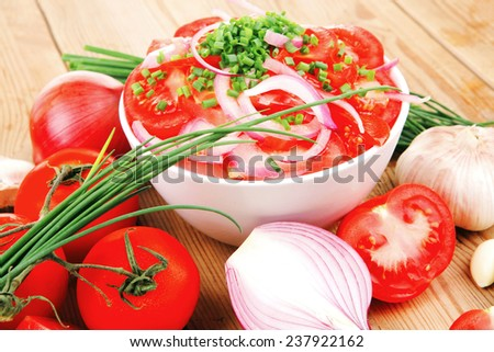 vegetable salad : fresh tomato salad in white bowl with bundle of chives , tomatoes on twig , onion, and garlic over wooden table - stock photo