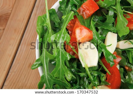 vegetable salad : green salad with raw tomato and garlic in white bowl over wood served with cutlery - stock photo