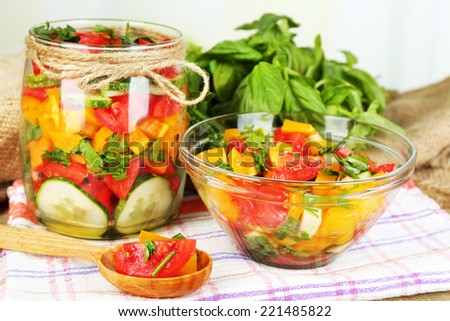 Vegetable salad in glass jar and bowl on wooden table, on bright background - stock photo