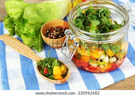 Vegetable salad in glass jar, on  napkin, on wooden background - stock photo