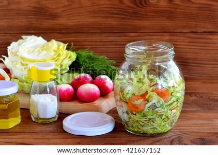 Vegetable salad in glass jar. Simple mixed vegetable salad. Salad with cabbage, carrots, radish, dill and olive oil. Salad with fresh vegetables recipe  - stock photo