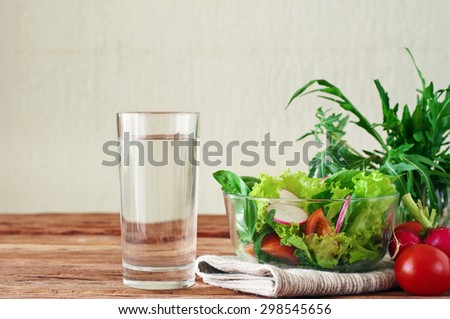 Vegetable salad with a glass of pure water on the wooden table. The concept of a healthy lifestyle and diet. Close-up. Copy space.  Free space for text - stock photo