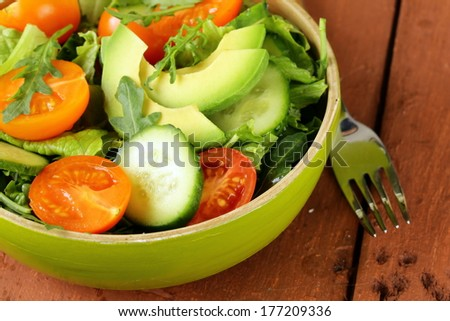 vegetable salad with avocado and tomatoes in rustic style - stock photo