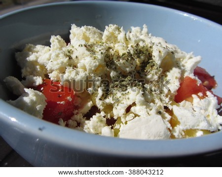 Vegetable salad with cheese served in a blue bowl. - stock photo