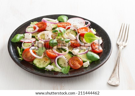 vegetable salad with feta cheese on white wooden table, horizontal - stock photo
