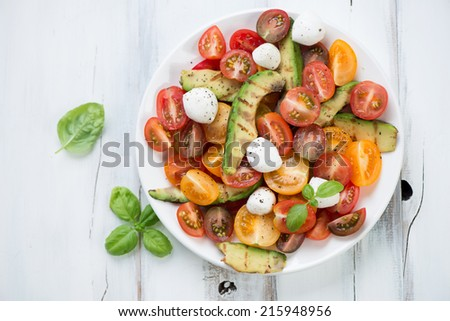 Vegetable salad with grilled avocado, tomatoes, cheese and basil