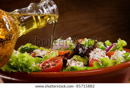 vegetable salad with olive oil pouring from a bottle - stock photo