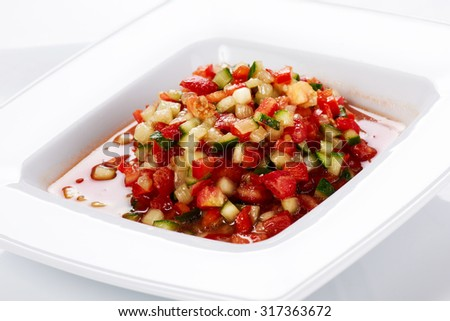 Vegetable salad with tomatoes, cucumbers, and onions, in a white plate.