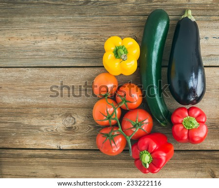 Vegetable set: ripe tomatoes, paprika, zucchini and an aggplant ob a rustic wooden background with a copy space - stock photo
