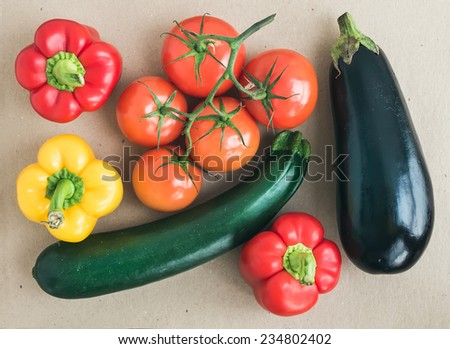 Vegetable set: ripe tomatoes, paprika, zucchini and an eggplant on a craft paper background  - stock photo