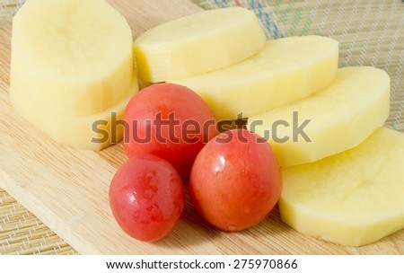 Vegetable, Slice Potatoes and Fresh Tomatoes on Wooden Cutting Board. - stock photo