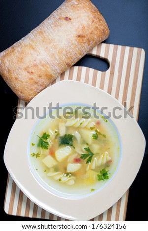 Vegetable soup and ciabatta on bamboo board - stock photo