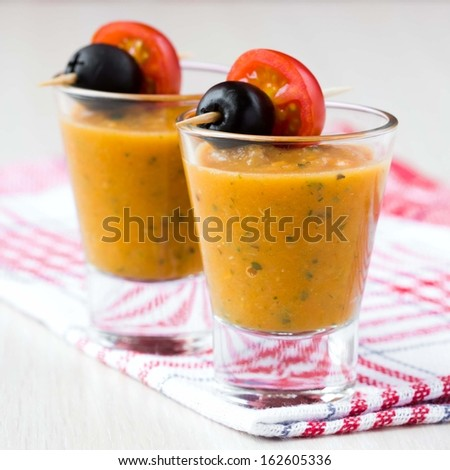 Vegetable soup in small glasses with olives and tomato, starter, tasty appetizer for guests - stock photo