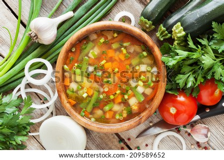 vegetable soup in wooden bowl and ingredients on wooden rustic table. top view - stock photo