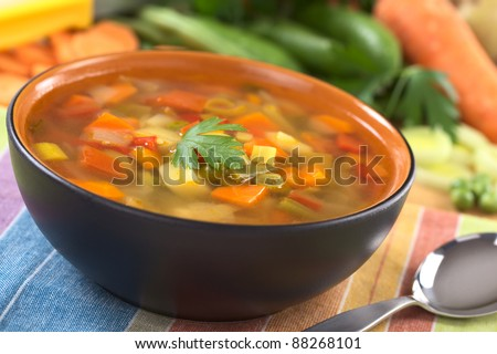 Vegetable soup made of green bean, pea, carrot, potato, red bell pepper, tomato and leek in black bowl garnished with a parsley leaf (Selective Focus, Focus on the front of the parsley leaf) - stock photo