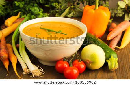 Vegetable soup surrounded by fresh vegetables. - stock photo