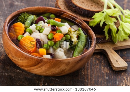 Vegetable soup with bean, pea, carrot and potato in wooden bowl - stock photo
