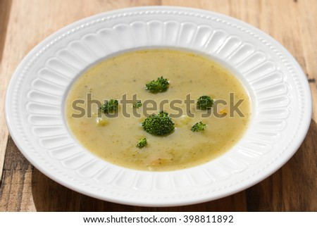 vegetable soup with broccoli on white dish on brown wooden background - stock photo