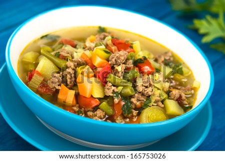 Vegetable soup with mincemeat, green bean, potato, leek, carrot, tomato and parsley served in blue bowl on blue wood (Selective Focus, Focus one third into the soup)  - stock photo