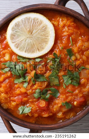 vegetable soup with red lentils and tomatoes macro on the table. Vertical view from above
