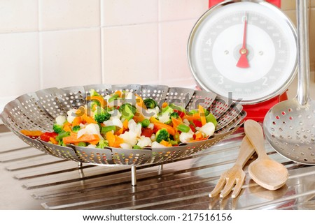 vegetable steamer with vegetables MIX INSIDE AND BALANCE OVER DRAINING BOARD - stock photo