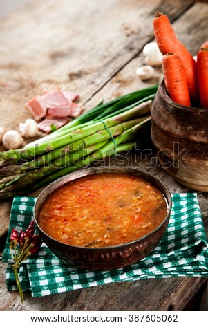Vegetable stew. Delicious soup with vegetables and spices on wood. - stock photo