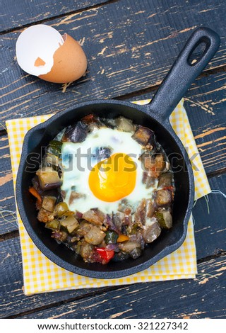 Vegetable stew with eggplant and egg in a batch cast iron pan, top view - stock photo