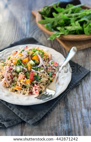 Vegetable tabbouleh with rainbow quinoa on wooden table with aubergine and arugula