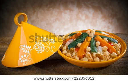 Vegetable Tajine with cous cous on wooden table. - stock photo