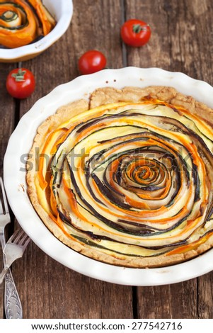 Vegetable Tart of carrots, zucchini and eggplant with bechamel sauce on a wooden table. Rustic style and selective focus - stock photo