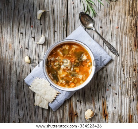 Vegetable vegetarian soup made of cabbage, corn, green bean, peas, carrots, cauliflower, green bell pepper, tomato and leek in a white bowl - stock photo