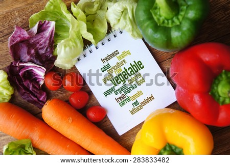 Vegetable word cloud arrangement concept on small white book with vegetables. - stock photo