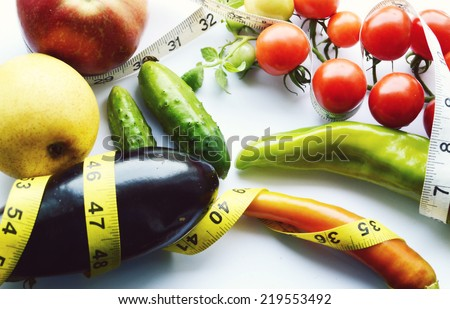 vegetables and fruits for weight loss, a measuring tape, diet, weight loss,cherry tomatoes, green peppers.eggplant.cucumber