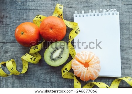 vegetables and fruits for weight loss, a measuring tape, diet, weight loss,notebook, diary, orange, tangerine, banana, kiwi - stock photo