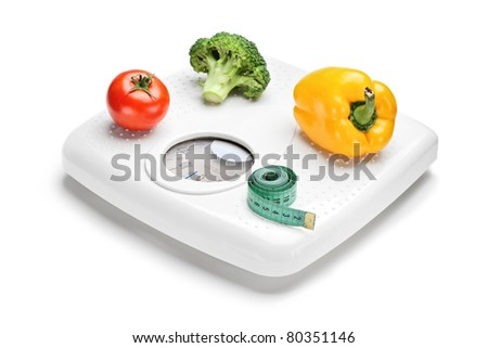 Vegetables and measuring tape on a weight scale isolated on white background - stock photo