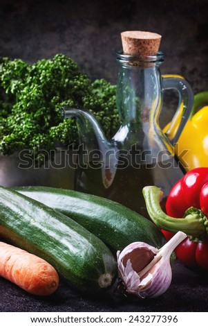 Vegetables and parsley with olive oil in glass bottle over dark background - stock photo