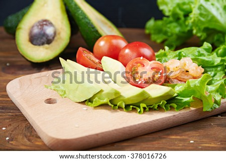 Vegetables avocado, tomato salad, and shrimps on a cutting board on a wooden background with avocado on a background - stock photo