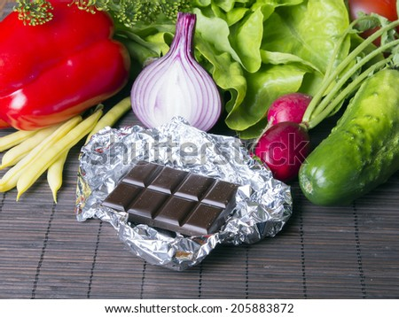 vegetables, candy and chocolate on wooden background - stock photo