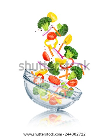 vegetables falling into a glass bowl on a white background. Concept slim figure - stock photo